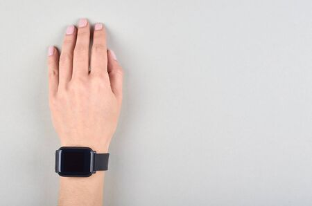 Hand with black smart watches on grey background. Flat lay, overhead view image. Copy space, template.
