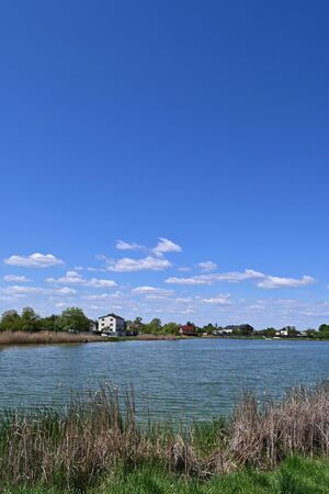Little village on lake shore, green trees and fluffy clouds on blue sky.