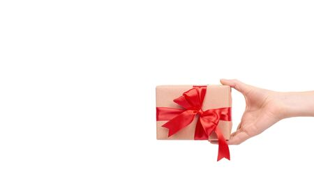 Hand with gift box, wrapped with brown paper. Isolated on white background. Copy space, template. Stock Photo