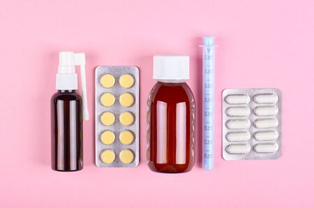 Baby antipyretic bottle and pills on pink background. Flat lay, overhead view image. Stock Photo