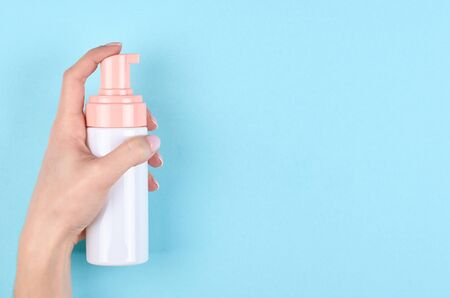 Hand with sanitizer bottle on blue background. Flat lay, overhead view image. Copy space, template.