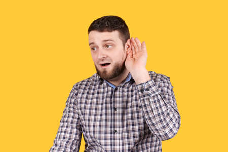Man listening with his hand on ear, hearing problems, isolated on orange background.
