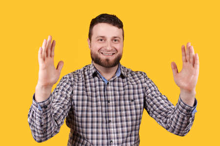 Man smiling and shoving size with hands, isolated on yellow background.