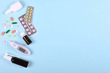 Medical pills, thermometer and spray bottle on blue background, flat lay, overhead view image. Medicine concept.