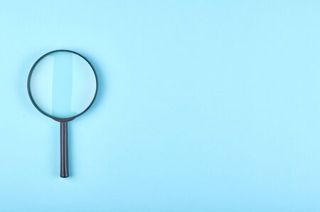 Black magnifying glass on blue background. Flat lay, overhead view image. Copy space, template.