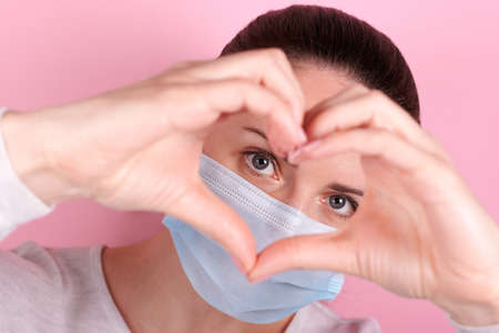 Portrait of a brunette girl in a medical mask shows heart with her fingers. Isolated on pink background.