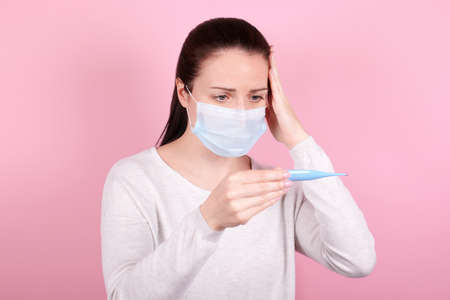 Portrait of a brunette girl in a medical mask looks at the thermometer. Isolated on pink background.
