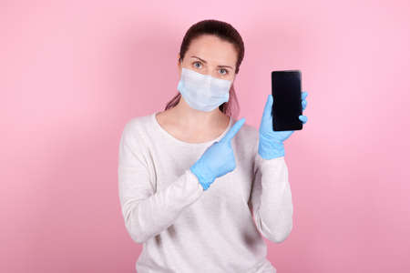 Portrait of a brunette girl in a medical mask and blue rubber gloves pointing on cellphone. Isolated on pink background.