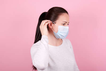 Portrait of a brunette girl, puts on a medical mask, side view. Isolated on pink background.