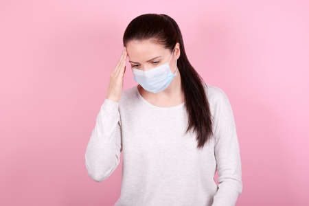 Portrait of a brunette girl with headache in a medical mask. Isolated on pink background.