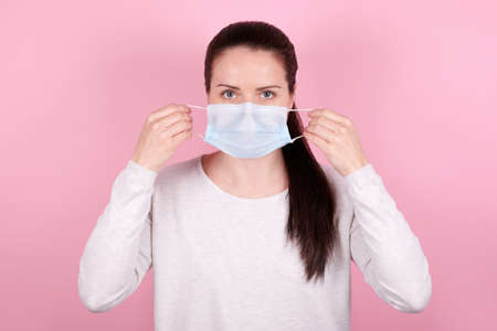 Portrait of a brunette girl, puts on a medical mask. Isolated on pink background. Archivio Fotografico