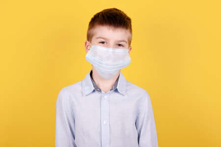 Portrait of a brunette boy in medical mask. Isolated on yellow background.
