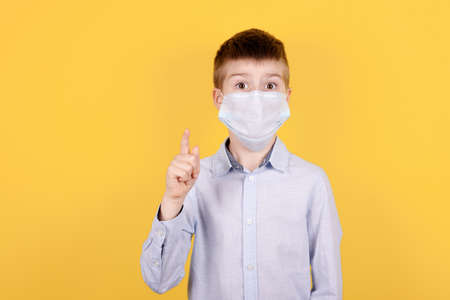Portrait of a brunette boy in medical mask pointing finger up, idea concept. Isolated on yellow background.