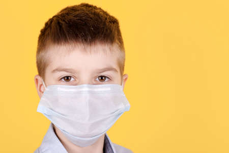 Portrait of a brunette boy in medical mask. Isolated on yellow background. Copy space.