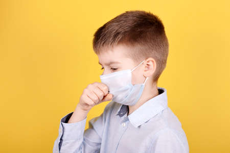 Portrait of a brunette boy in medical mask coughs. Isolated on yellow background. Archivio Fotografico