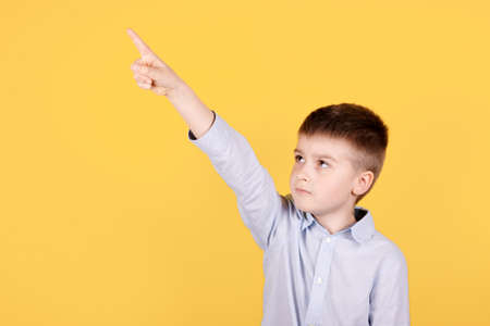 Portrait of a brunette boy pointing hand and finger up. Isolated on yellow background.