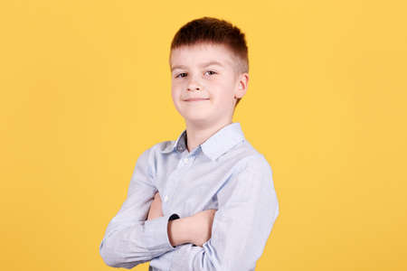 Portrait of a confident brunette boy, looking at camera, crossed hands. Isolated on yellow background.