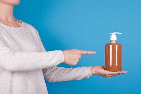 Brown liquid soap in bottle in hand on blue background. Finger pointing on object. Reklamní fotografie