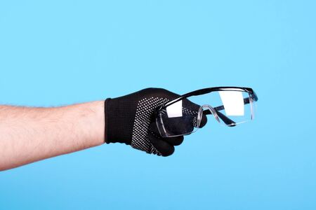 Hand with working glove holding protective glasses. Reklamní fotografie