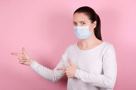 Portrait of a brunette girl in a medical mask pointing to the side with hands.