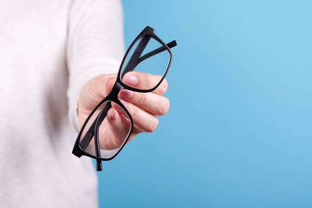 Glasses in a hand on a blue background. Close up photo.