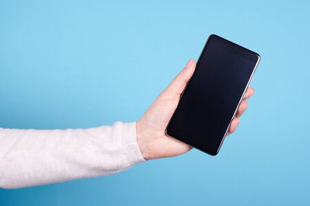 Mobile phone in hand on a blue background.