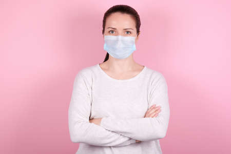 Portrait of a brunette girl in a medical mask with crossed hands. Isolated on pink background. Archivio Fotografico