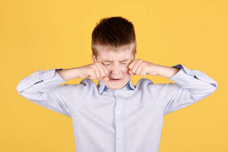 Portrait of a brunette boy crying with hands.