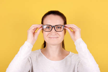 Portrait of a brunette girl puts on glasses. Isolated on pink background.