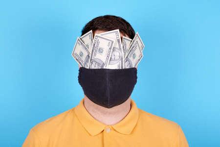 Brunette man in protection mask, paper money on the face. 免版税图像