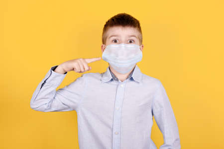 Portrait of a brunette boy in medical mask pointing with finger on face. Isolated on yellow background.