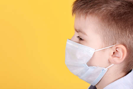 Portrait of a brunette boy in medical mask, side view. Isolated on yellow background. Copy space.