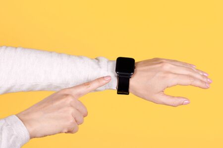 Black smart watch on hand on yellow background. Finger pointing on object.