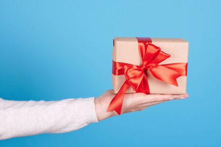 Present box with red ribbon in hand. Reklamní fotografie