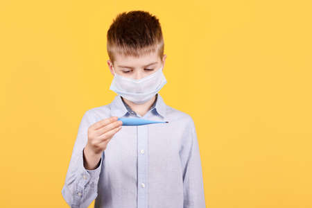 Portrait of a brunette boy in medical mask looks at the thermometer.