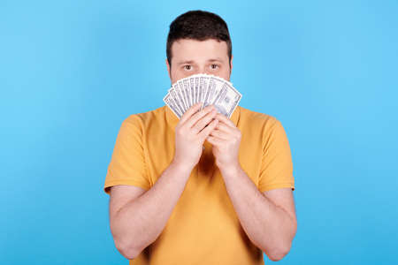 Brunette man holding pile of paper money. Archivio Fotografico