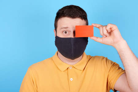 Brunette man in protection mask holds red credit card in hand.