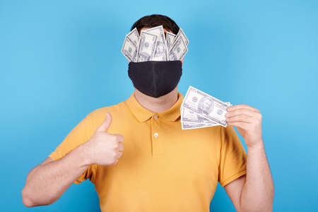 Brunette man in protection mask, paper money on the face. Archivio Fotografico