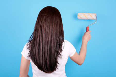 Brunette girl with long hair using paint roller, view from behind. Archivio Fotografico