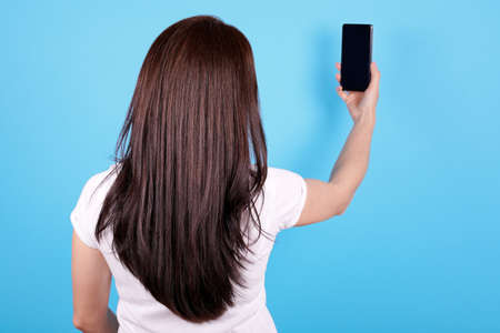 Brunette girl with long hair using mobile phone, view from behind. Archivio Fotografico