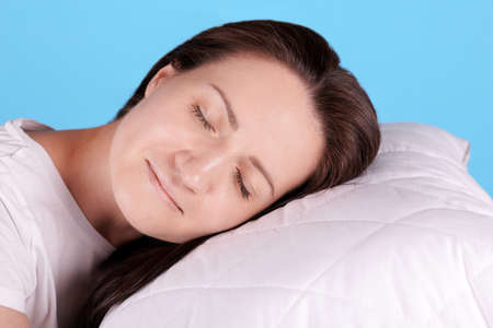 Brunette girl sleep on white pillow, closed eyes.