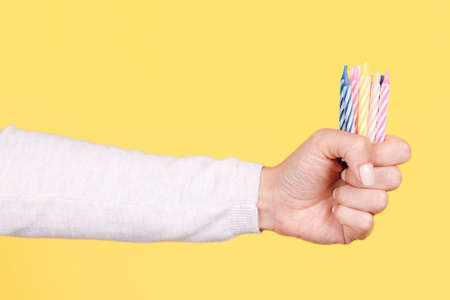 Hand with colored birthday candles.