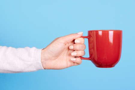 Hand with red mug with handle.