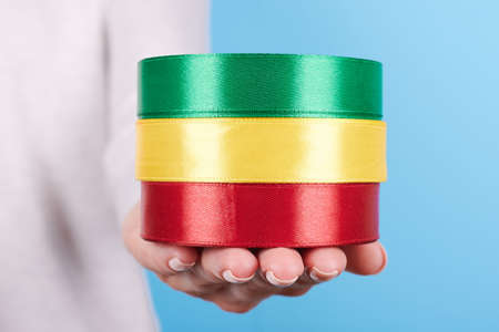 Hand with colored ribbon rolls.
