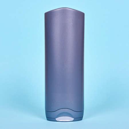 Gray shampoo bottle. Blue background.