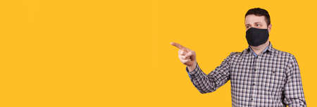 Man in black face mask pointing with finger, isolated on orange background. Coronavirus concept, copy space template, banner.