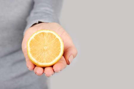 Hand with half lemon on grey.