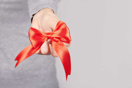 Hand with red ribbon on grey. Stock fotó