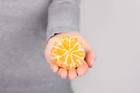 Hand with fresh tangerine on grey.