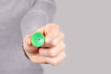 Hand with green sewing button on grey. Stock fotó